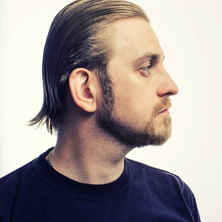 Photo pour Portrait of an attractive blond hipster beard in profile on a gray background - image libre de droit