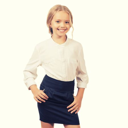 Photo for Lovely nine year old schoolgirl in a shirt and a skirt posing isolated on white - Royalty Free Image