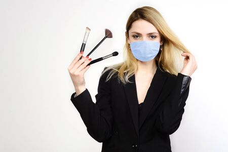 Foto de Attractive blonde Make-up artist in mask holding brushes on white background, Coronavirus Outbreak Defense Concept - Imagen libre de derechos