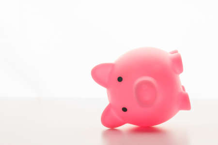 Photo pour pink piggy bank lying on its side isolated on white background - image libre de droit