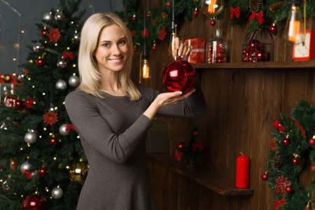 Foto de Beautiful young woman decorates a Christmas tree with balls in the New Year home interior. - image - Imagen libre de derechos