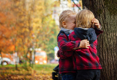 Photo pour Two child boys in identical red shirts in a cage are hugging in an autumn park - image libre de droit