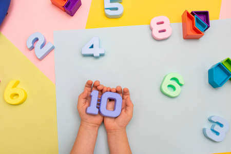 Photo pour The child plays with multi-colored numbers. Childs hands hold numbers top view on colored pastel background - image libre de droit