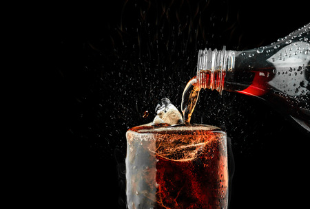 Photo pour Pour soft drink in glass with ice splash on dark background. - image libre de droit