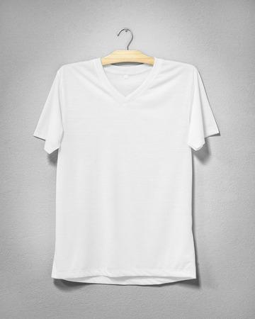 Photo pour White shirt hanging on cement wall. Empty clothing for design. Front view. - image libre de droit