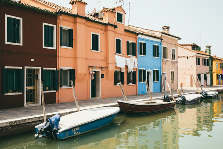Burano, Venice, Italy - July 2, 2018: Panoramic view of brightly coloured homes and water canal with boats in Burano, it is an island in the Venetian Lagoon. People walk and rest on streets