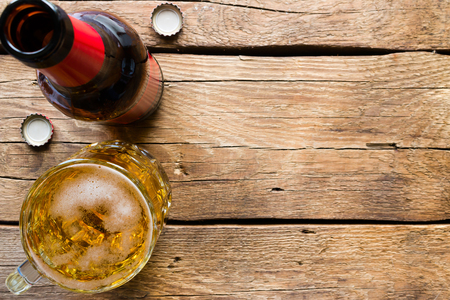 Photo pour glass bottle and a mug of light beer on a wooden background space for text - image libre de droit