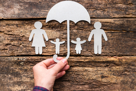 Photo pour A man holds an umbrella over his family - a concept of protection and insurance - image libre de droit