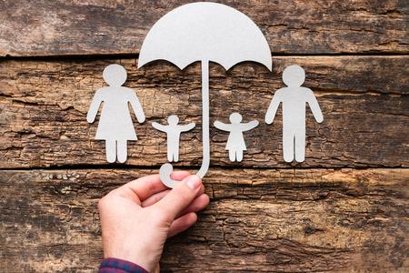 Foto de A man holds an umbrella over his family - a concept of protection and insurance - Imagen libre de derechos