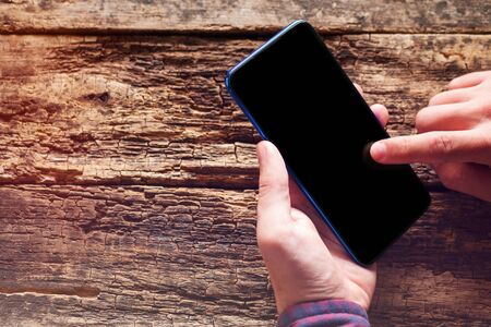 Photo pour man holds a mobile phone with a blank black screen. reads smartphone screen messages. on a wooden background with place for text mockup - image libre de droit