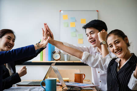 Photo pour Business team giving a high fives gesture as they laugh and cheer their success. Achievement and Business Goal Success Concept. soft focus. - image libre de droit