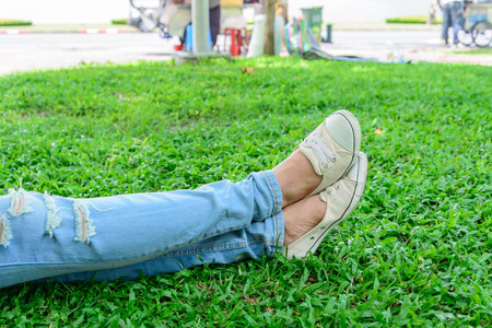 Cropped woman legs in denim with white sneakers resting on grass.