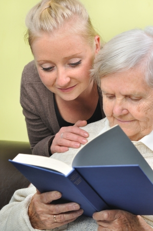 Senior woman with her caregiver in home reading book