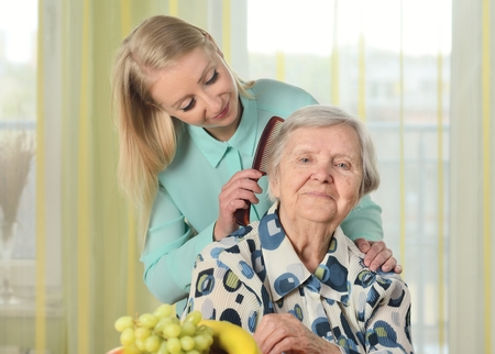 Senior woman with her caregiver in home.