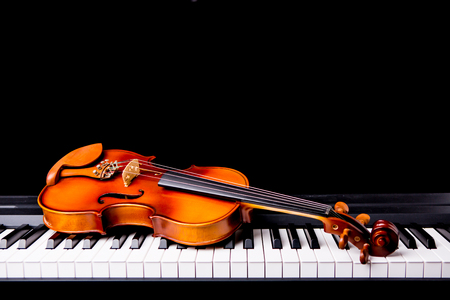Photo pour Violin on the piano on a black background - image libre de droit