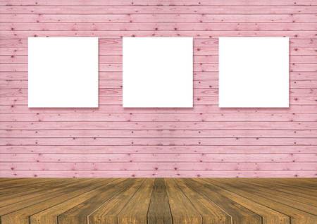 Wooden board empty table in front of Three canvas frame on pink pastel wooden wall for image advertising. Perspective brown wood with old wall and lighting drop, can be used for display or present your products.Mock up your productsroom interior,Three emp