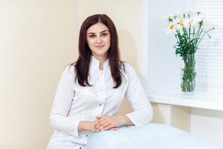 Foto de Portrait of female brunette cosmetologist in uniform near the window in the cosmetology office - Imagen libre de derechos