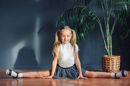 Photo pour Beautiful little blonde girl with hair gathered in tails, white t-shirt, white socks and gray skirt sitting on twine at home looking at camera and smiles - image libre de droit