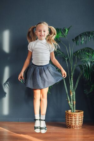 Photo for 8 years old Beautiful little blonde girl with hair gathered in tails, white t-shirt, white socks and gray skirt jumping in a child room at home, still life photo - Royalty Free Image