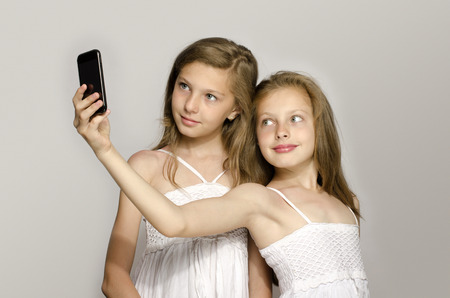 Two young girl taking a selfie, kids taking a photo and having fun, girls playing with a mobile phoneの写真素材