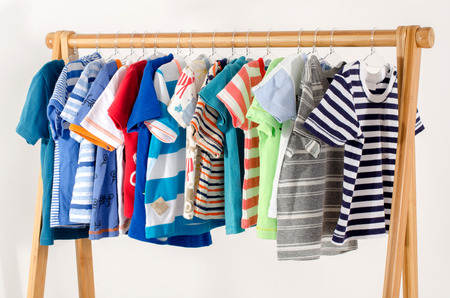 Photo pour Dressing closet with clothes arranged on hangers.Colorful wardrobe of newborn,kids, toddlers, babies full of all clothes.Many t-shirts,pants, shirts,blouses, onesie hanging - image libre de droit