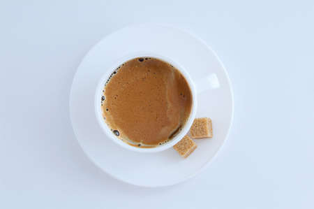 Photo pour White cup of coffee with froth and cane sugar cubes on a saucer on a white background. - image libre de droit