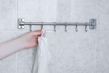 Photo pour Hangs a white towel on a metal hanger in the bathroom. - image libre de droit