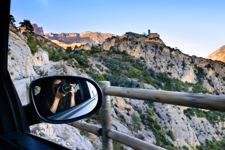 Enjoying travel. Tourist girl on a trip, photographing from a car window, lifestyle concept adventure, traveler with backpack on background mountain landscape and a medieval castle, young girl traveler with a camera.