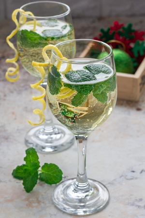 Spritzer cocktail with white wine, mint and ice, decorated with spiral lemon zest, vertical