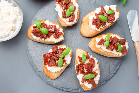 Photo for Bruschetta with sun dried tomato, feta and philadelphia cheese and basil on a stone plate, horizontal, top view, closeup - Royalty Free Image