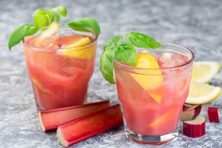 Photo pour Refreshing lemonade with rhubarb, lemon, sparkling water and basil in a glass, horizontal - image libre de droit