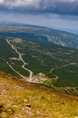 Mountain paths leading to an isolated mountain cottage in cloudy weather