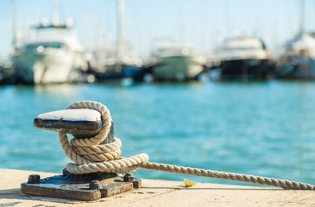 Photo pour Mooring rope and bollard on sea water and yachts background - image libre de droit