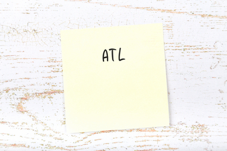Yellow sticky note with handwritten text atl