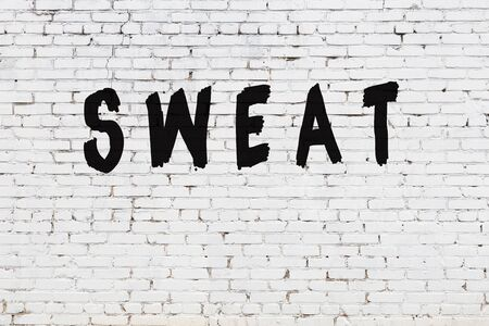 Word sweat written with black paint on white brick wall.