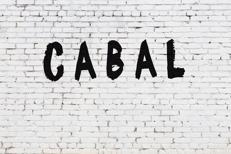 Word cabal written with black paint on white brick wall.