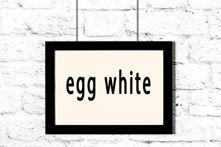 Photo pour Black wooden frame with inscription egg white hanging on white brick wall - image libre de droit