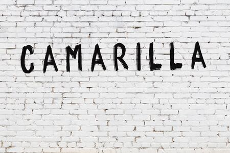 Word camarilla written with black paint on white brick wall.