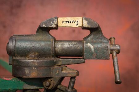 Concept of dealing with problem. Vice grip tool squeezing a plank with the word crony