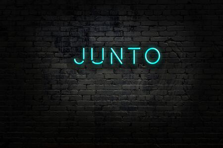 Neon sign with inscription junto against brick wall. Night view