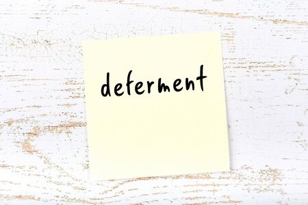 Photo pour Yellow sticky note on wooden wall with handwritten inscription deferment - image libre de droit