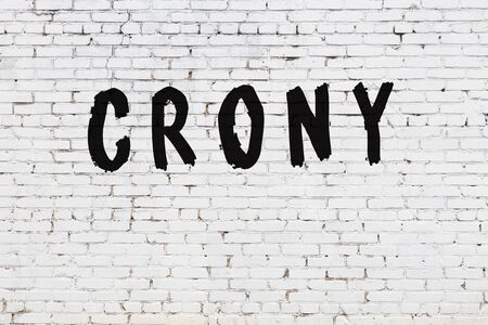 Word crony written with black paint on white brick wall.