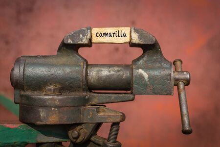 Concept of dealing with problem. Vice grip tool squeezing a plank with the word camarilla