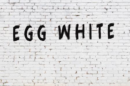 Photo pour White brick wall with inscription egg white handwritten with black paint - image libre de droit
