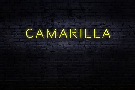 Neon sign on brick wall at night. Inscription camarilla