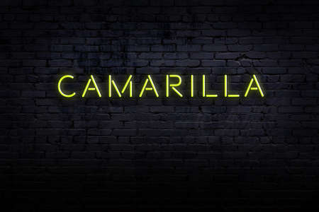 Neon sign with inscription camarilla against brick wall. Night view