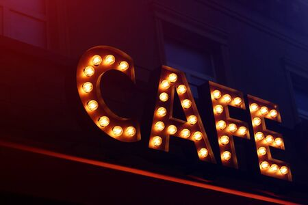 Photo pour Sign from light bulbs with the word CAFE in the night city, toned - image libre de droit