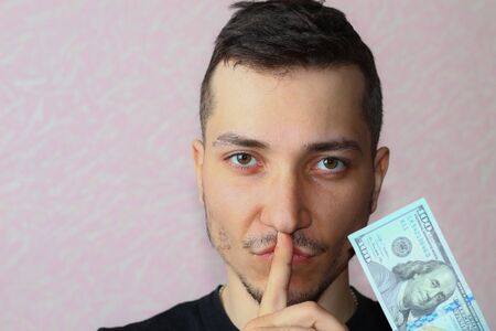 Young man symbolically closes his mouth. Concept of silence for money.