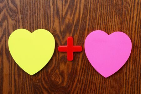 Photo pour Two blank heart shaped stickers with plus sign. Creative symbolic background on the theme of love - image libre de droit