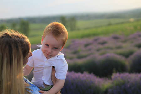 Photo pour Lifestyle photo shoot of a real family in nature. Mom and son enjoy a stroll through the fresh air and scent on a lavender field in the rays of the setting sun. Selective focus. - image libre de droit